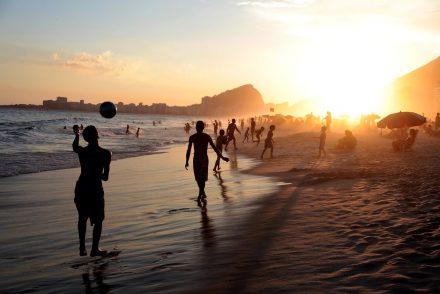 Fim de tarde em praia do Rio de Janeiro com pessoas na areia